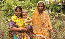 Woman holding child standing with mother-in-law outside