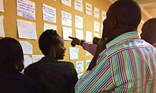 "Photograph of several women and men looking at notes posted on a large bulletin board and having a discussion. Caption: ""CHAIN partners reflect on joint activities they developed during a November 2016 workshop."""