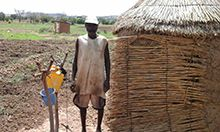 Photo of a man, Tengdo Kuzoba, standing by his latrine and tippy tap.