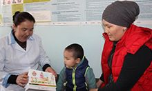 "Photo of a mother, her child, and a nurse at a health facility looking at information on nutrition. Caption: ""Mairam Usupova, Head Nurse at the Family Group Practice in Naryn, counsels a mother on maternal nutrition and dietary diversity."