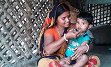 Woman holding and feeding her toddler