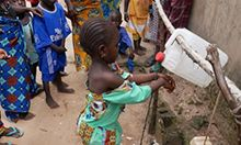 "Photo of a child washing her hands with a tippy tap as several other children look on. Caption: ""Children in the village of Touba Mourid have fun practicing proper hygiene by washing their hands at a special handwashing station or tippy tap."""