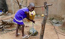 A young child grins at the camera as she washes her hands at a tippy tap.