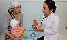 A doctor counsels a woman holding a baby on proper nutrition