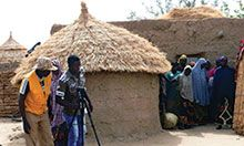 Two men and a woman set up a shot in front of a hut with a video camera. A group of villagers watches from between the hut and a straw wall.