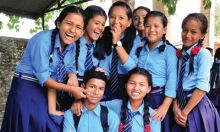 Photo of a group of adolescents smiling and huddling together to pose.