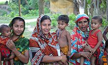 Photo of three mothers, standing outside, each holding her child while looking at the camera.