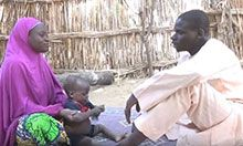 A couple sits and talks about breastfeeding as the mother tries to keep the baby on the blanket.