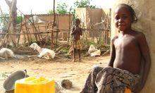 Image of child sitting outside house