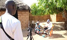 Two community members being filmed eating a delicious meal containing orange-fleshed sweet potato.