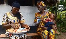 A mother prepares healthy food for her baby. The grandmother, holding the fussy baby, looks on.