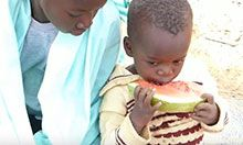 A mother looks on as her child eats a slice of watermelon