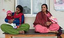 Two Nepali women sit cross-legged on a bench outside what looks like a clinic. One woman holds a roughly 6 month old baby in her lap.