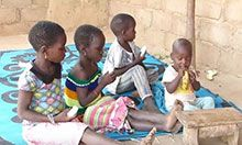 Four children sit outside and happily eat bananas