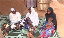 Health worker and two new mothers sitting on a rug and talking