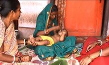 woman feeding young child