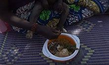We see the legs of a seated mother and baby with the main focus of the picture on a bowl of diverse fruits and vegetables she is feeding her child.