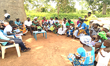 Group photo of a mother-to-mother support group: a large group of women and men sit in plastic chairs in a circle.