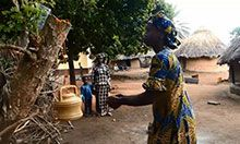 A woman washes her hands at a tippy tap hung from a tree branch