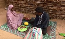 A Wife and Husband sit on a rug and discuss the family's monthly food consumption