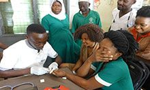 A health worker calmly uses a Hemocue device on a patient. The patient covers her face with her hand and has a pained look on what we can see of her face. Two friends of hers look on with similar uncomfortable looks.