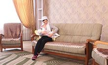 A woman sits on a couch and breastfeeds her infant