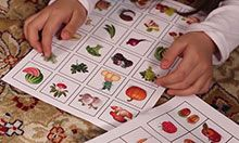 children sit on the floor and look at sheets of paper with images of fruits and vegetables on them