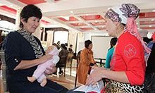 Photo credit: SPRING/Kyrgyz Republic. Two women sitting and talking in a large room with others doing the same. One woman holds cards about nutrition and is counselling the other women who is holding a realistic baby doll and practicing the proper way to hold an infant.
