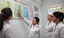 Photo of a group of women in medical coats pointing to charts on a wall.