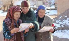 Photo of three women looking at the toolkit materials.