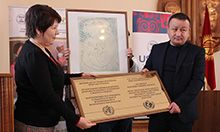 Photo of two people posing with a large plaque. USAID Health Project Management Specialist Aisha Zhorobekova presents the BFHI certification plaque to Abdulbaki Yrysbekov, Director of Karakul General Medicine Practice Center in Jalalabad oblast.