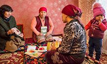 Photo of a mother and her child looking over materials and receiving counseling from two health professionals