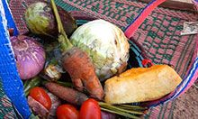 a basket of local foods including several root vegetables, tomatoes, and cabbage