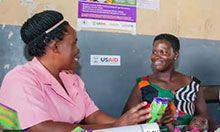 Two women sit and talk. One woman holds a packet of micronutrient powder and explains its benefits to the other woman.
