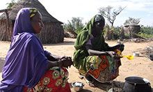 Two women crouch over a pot on a fire. One woman is stirring the moringa in the pot.