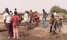 Photo of a group of men and boys working with shovels and tools.