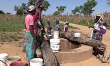 Photo of a group of women and children at a water well, collecting water in buckets.