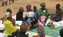 Photo of women seated outside looking at illustrated diagrams