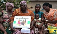 Photo of several women seated and holding an illustrated diagram.