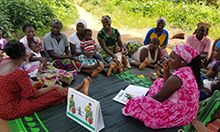 Photo of a gathering of women sitting in a circle with counseling materials sitting on the grass in the foreground