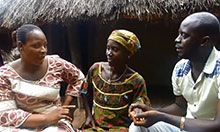 A health worker, pregnant woman, and the pregnant woman's husband sit together on a bench and talk.