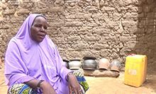 Photo of a woman sitting with water containers in front of a wall.