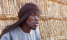 Photo of a man in front of a straw wall.