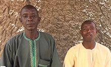 Photo of two men standing in front of a stone wall.