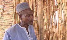 Photo of a man standing in a straw enclosure.
