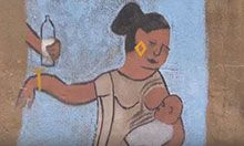 A chalk drawing on a wall of a mother breastfeeding her infant and pushing away someone's hand holding a bottle of milk.