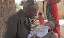 A father grins at his infant. He holds the baby in his lap and supports its neck.