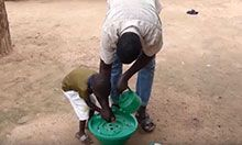 A man and his young son bend over a bowl to wash their hands. The father is teaching the son how.