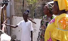 Three older women watch as a school-aged girl shows them how to use a tippy tap.