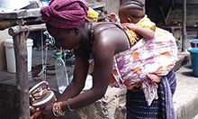 Cover photo: a mother in Sierra Leone bending down, carrying her infant child on her back as she uses a tippy-tap to wash her hands